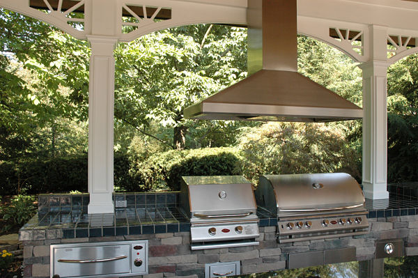 outdoor kitchen with stainless steel grills and hood