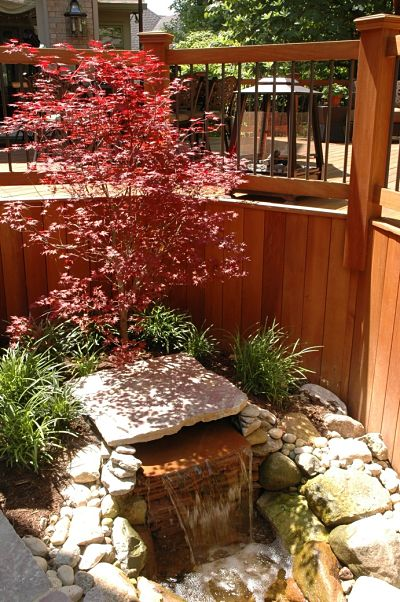 garden waterfall feature bordering composite deck