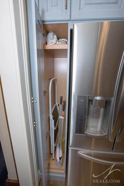 narrow broom closet next to fridge