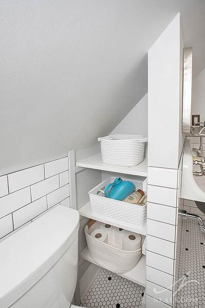 A niche in a bathroom filled with shelving for storage