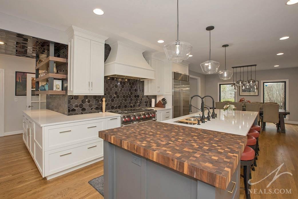 Kitchen with island and range showing the butcher block detail and bold black tile backsplash