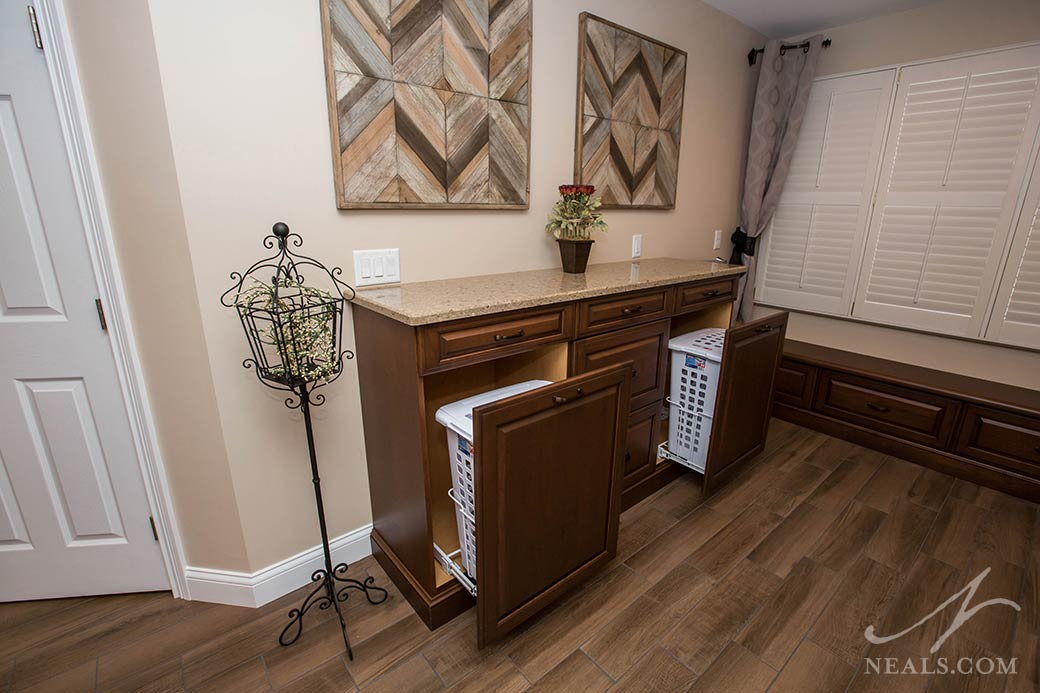 A storage cabinet across from the shower in this Maineville bathroom holds two clothes hampers.