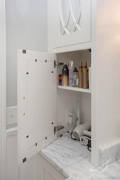 A cabinet on this Indian Hill bathroom vanity provides an outlet and space for daily personal care tools.