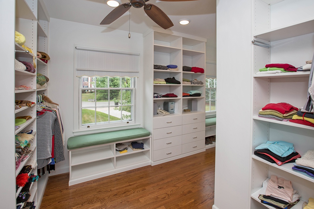 A built-in bench in this Hyde Park closet makes use of the space under a window and adds more shelving.