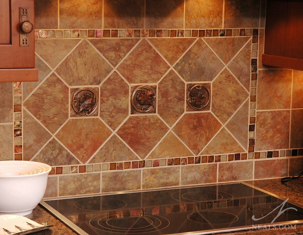 A mixture of natural stone tiles, artisan glass mosaic tiles, and accent tiles featuring a leaf design create an up-to-date take on the Craftsman backsplash.