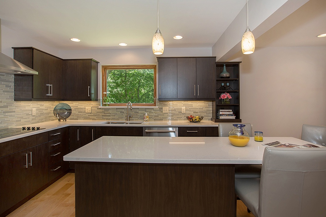 The minimal cabinetry, slim hardware, and playful glass backsplash of this Cleves kitchen are in line with contemporary design.