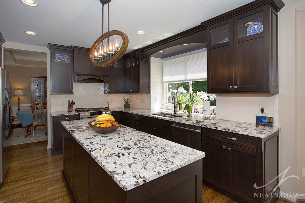 This transitional style kitchen in Loveland mixes contemporary lighting and hardware with a traditional backsplash design and cabinetry trim.