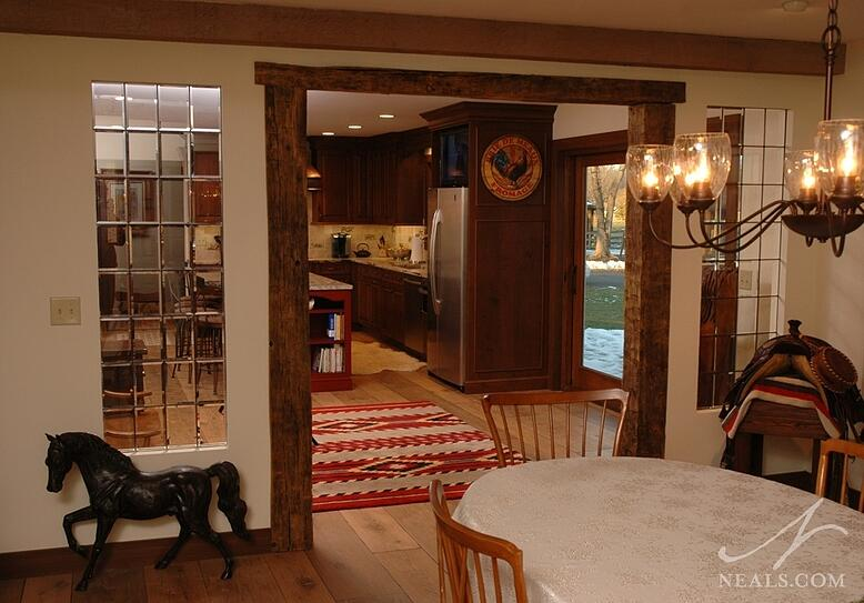 In this remodel, a worn wood archway, wide-plank flooring, exposed beams and unpainted wood trim create a classic country look.