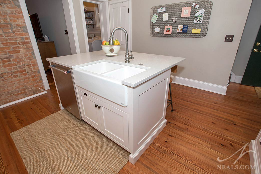 This small island in a Newport kitchen holds a sink, dishwasher and room for seating on the other side.