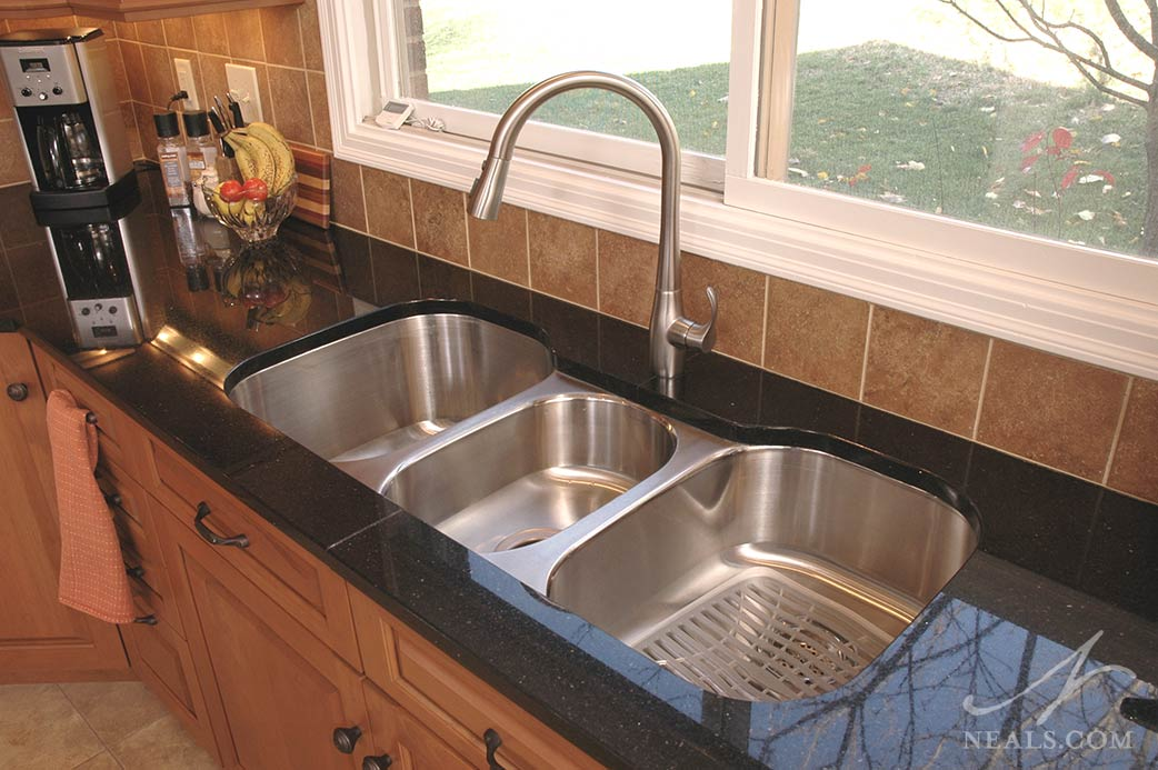 A stainless steel triple bowl kitchen sink in this West Chester kitchen.