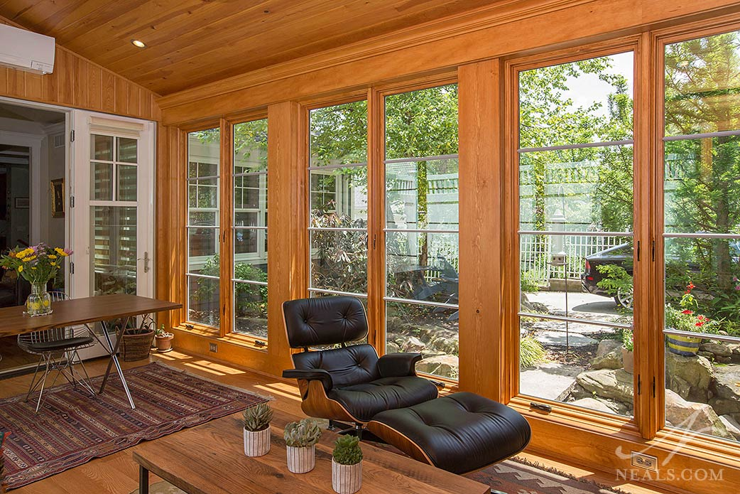 A sunroom in Madeira is a warm space with views to a well-appointed backyard garden.