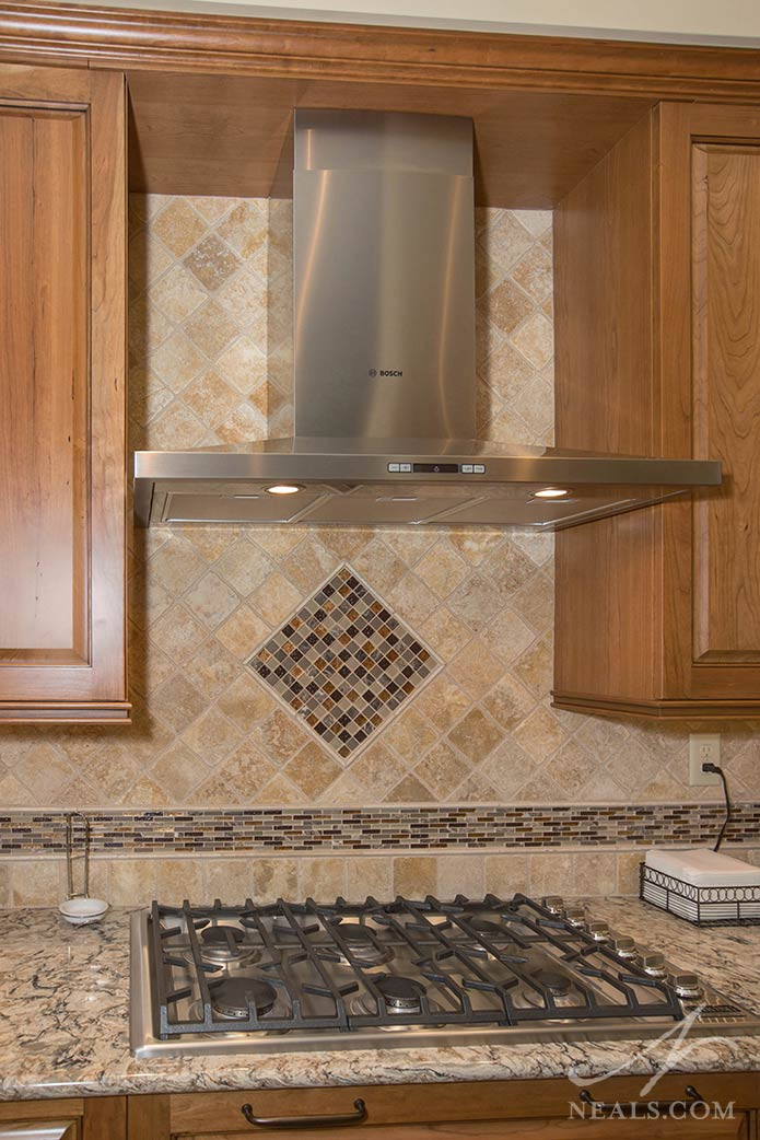 A tile backplash works with the hood to create a focal point in this Lebanon kitchen remodel.