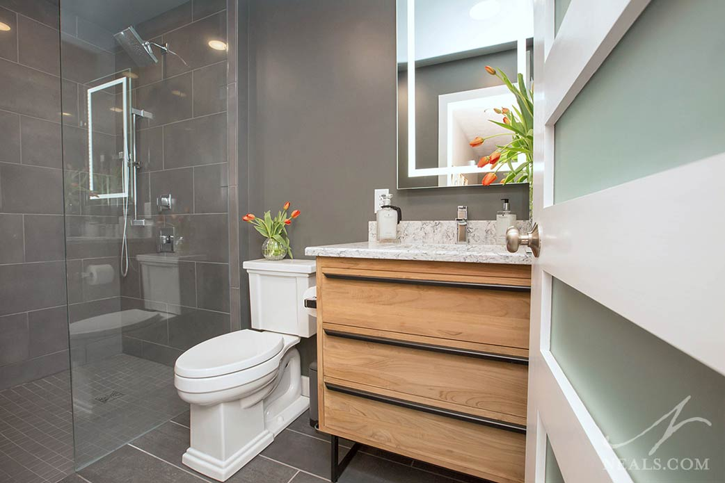 Integrated lighting in the vanity mirror in this Anderson Township bath.